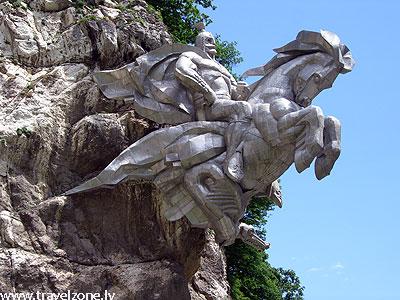 памятник Уастырджи (Осетия) Памятник Уастырджи, Россия, Осетия, Алагирское ущелье. Транскавказская автомагистраль – одна из главных дорог, связывающих Россию с Закавказьем. Она проложена по живописному Алагирскому ущелью Осетии. Шоссе то прижимается к отвесным скалам, то ныряет в тоннель, пробитый в толще камня. Недалеко от города Алагира, за очередным поворотом над дорогой нависает один из самых грандиозных памятников Осетии – многотонная статуя Уастырджи, самого почитаемого святого осетин. Этот памятник поражает своей мощью, силой и энергетикой. Уастырджи, верхом на коне, как будто замер, выскакивая прямо из скалы. Памятник Уастырджи создан в 1995 году по проекту Ходова Н.В. в дар народу Осетии. Один из самых больших конных памятников в мире. Его вес составляет 28 тонн. В ладони святого Уастырджи спокойно может поместиться человек. К месту установки скульптуру перевозили вертолетом. памятник Уастырджи (Осетия)Через несколько лет после установки вся скульптурная композиция сильно наклонилась вбок и грозила обрушиться. Для проведения восстановительных работ нанимали бригаду альпинистов. Уастырджи – самое почитаемое божество в осетинской мифологии, покровитель мужчин, путников, но более всего воинов. В нартском эпосе Уастырджи изображается в виде зрелого бородатого мужчины, грозного воина в боевом облачении, верхом на белом коне. С приходом в Осетию христианства, образ святого Уастырджи стали ассоциировать со Святым Георгием, который у христиан также почитался как покровитель воинов и путников. Но, кроме схожих функций, больше ничего общего у этих двух святых нет.памятник Уастырджи (Осетия) По легенде, многие народы Кавказа, в том числе и осетинцы, произошли от мифических богатырей нартов. Начиная далеких 8-7 веков до нашей эры, сказания о нартах, о происхождении и их приключениях постепенно сложились в нартский эпос. Уастырджи является одним из главных героев нартского эпоса, небожителем, часто посещающим нартов, помогающим тем, кто этого достоин. В сказаниях Уастыр